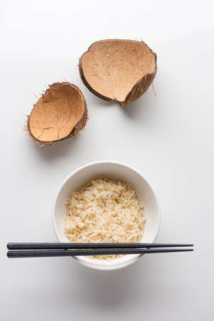 A closeup shot of cooked rice in a white plastic bowl with chopsticks on it on a white background