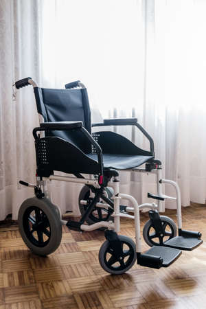 A vertical shot of an empty wheelchair in a room with wooden floors and bright white drapes