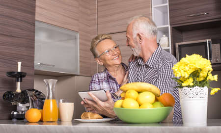 An elderly retired couple watching a video together on a tablet in a kitchen