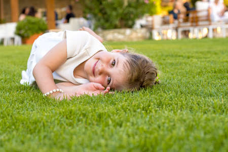 A smiling caucasian female child lying down on the grass in the park