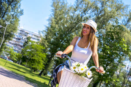 A closeup shot of a caucasian female riding a bike in the park with a basket of flowers in front