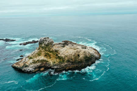 An aerial drone shot of a small rocky island in the blue beautiful ocean 写真素材