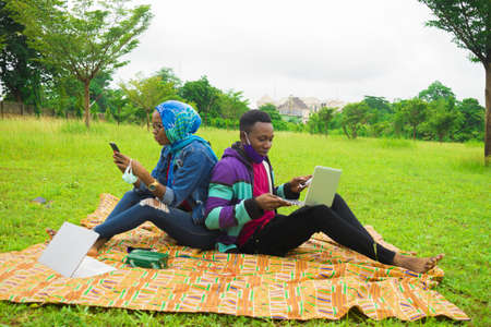 A happy Nigerian couple using their laptops and cellphones while on a picnic on a grassy meadow