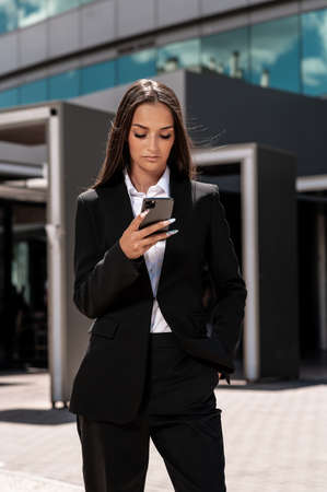 A vertical shot of a young Hispanic businesswoman checking her phone in front of an office building