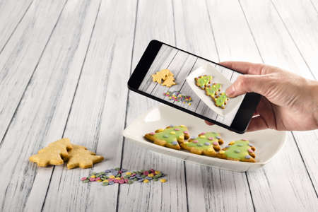 A high angle shot of a person taking a picture of some christmas cookies with his smartphone