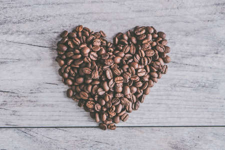 A closeup shot of coffee beans in shape of a heart on a gray wooden background 版權商用圖片