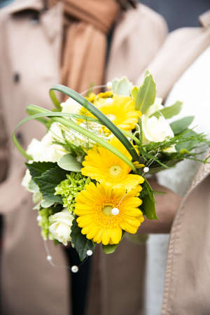 A vertical shot of a person holding a yellow flower bouquet with a blurred background