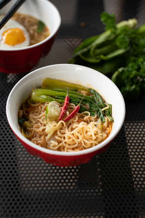 A vertical shot of soup with noodles and vegetables in a red bowl with a blurred background