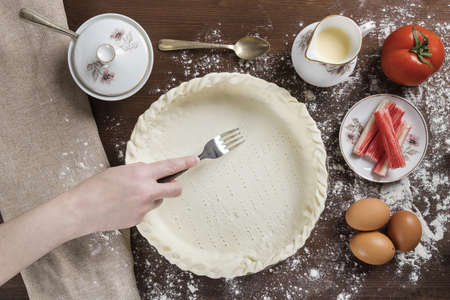 A high angle shot of a chef creating small holes on a dough base with a fork next to some ingredients