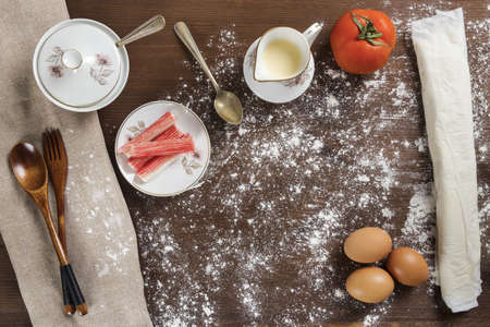 A high angle shot of a tomato, eggs, flour, and other ingredients on a wooden surface