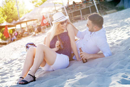 A shallow focus shot of a young Caucasian romantic couple drinking beer in the beach Zdjęcie Seryjne