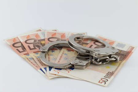 A close up shot of 50 value money bills with handcuffs on top isolated on a white background - corruption concept