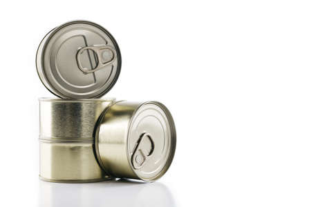 A closeup shot of round metal blank cans stacked on each other with one on its side on a white background Stock fotó