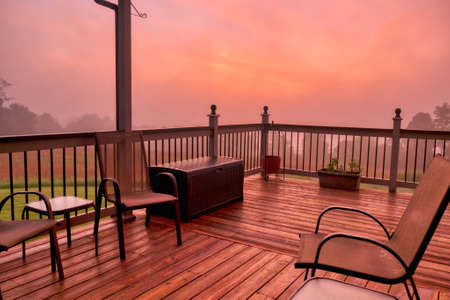 A beautiful wooden front porch of a countryside house to relax and enjoy amazing sunsets with friends and family