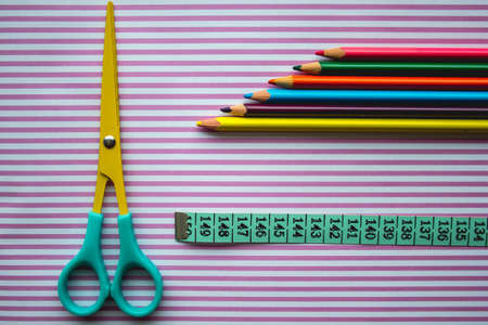 An overhead shot of a scissors color pencils and measuring tape on a striped surface Stock fotó