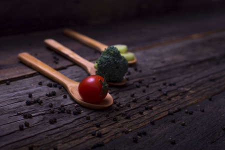 A closeup of wooden spoons with cherry tomatoes, broccoli and leek on a wooden table