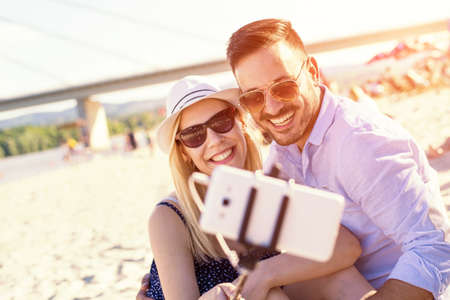 A shallow focus shot of a young Caucasian romantic couple taking a selfie in the beach
