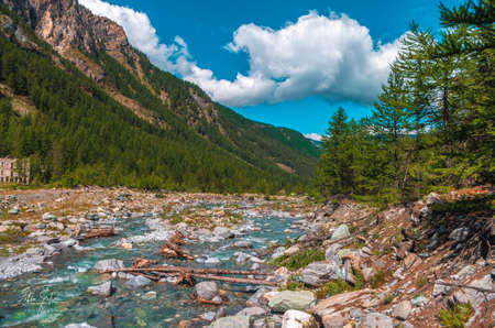 A beautiful scenery of a river with rocks near high mountains covered with green grass in  Pragelato, Italy