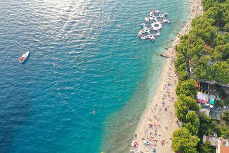 An aerial shot of people enjoying the beach at daytime in Makarska, Croatia