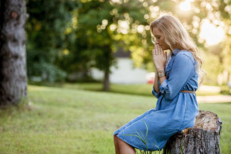 A blonde woman sitting on a tree stump and praying in a garden under sunlight