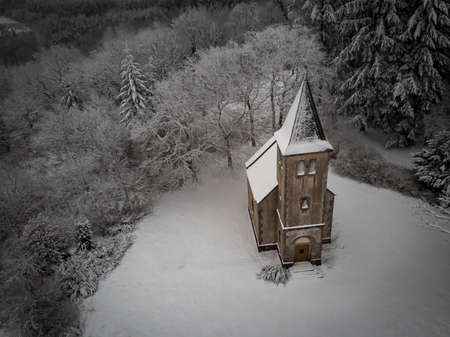 An aerial shot of a church covered in the snow surrounded by leafless trees Stock Photo