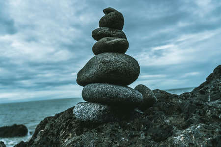 A closeup shot of perfectly balanced different sized rocks at the coast of the sea - perfect for stability depiction articles