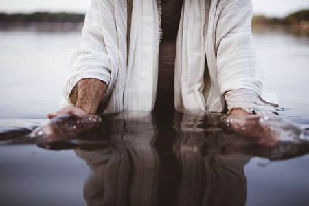 A closeup shot of a male wearing a biblical robe with his hands gathering water Stock Photo