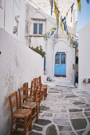 A vertical shot of a beautiful bystreet with flags hanged in the air in Paros, Greece