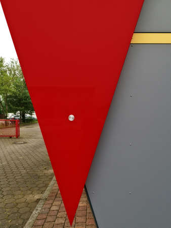 A low angle shot of a triangle-shaped red banner on a grey wall with a yard scene on the left Stockfoto