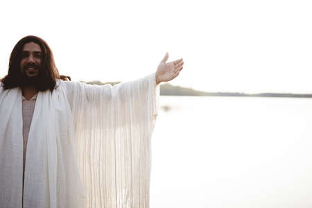 The Jesus Christ with his hands up towards the sky while looking at the camera