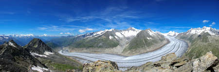 A beautiful panoramic shot of a road going through snowy Aletsch Glacier in Switzerland. Perfect for Switzerland travel scenarios.