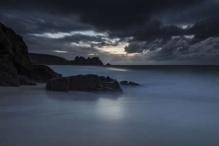 A dark mysterious scenery of the ocean and rocks surrounding it in Porthcurno, Cornwall, UK