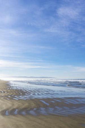 A vertical shot of a wet beach shore under a blue cloudy sky at daytime