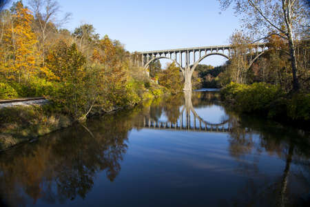 A beautiful shot of a bridge reflecting in the Cuyahoga River in Ohio on a beautiful autumn day