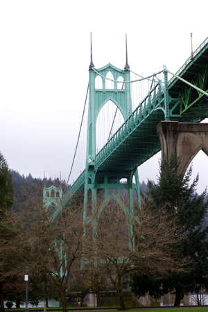 A vertical low angle shot of the famous St. Johns Bridge surrounded by a forest in Portland, Oregon, United States