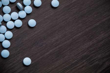 A closeup shot of blue round pills on the dark gray table Stock fotó - 154823142