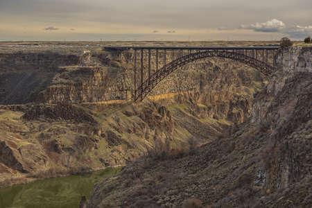 A beautiful shot of a bridge in the middle of cliffs with a cloudy sky in the background Stockfoto
