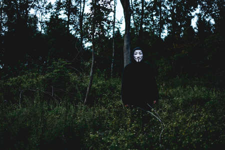 Black hooded person wearing white mask standing among green grass and trees in a forest Banque d'images