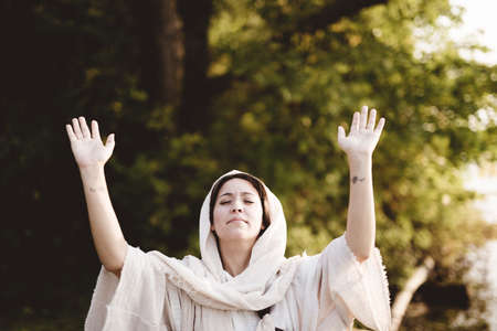 A shallow focus shot of a female wearing a biblical gown whit her hands up towards the sky