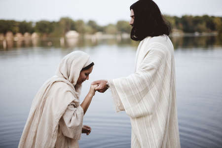 A shallow focus shot of a female wearing a biblical gown while holding the hand of Jesus Christ