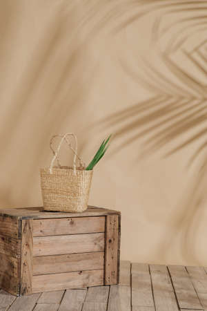 A vertical shot of a straw bag, with a green plant inside, on a wooden box, with a cream background. Perfect for depicting fashion scenario