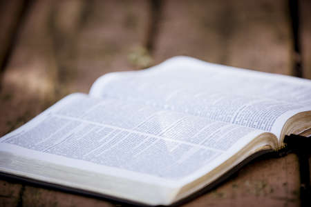 A selective focus shot of an open bible on a wooden surface with a blurred background