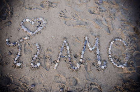 An overhead shot of sand on beach with stones spelling