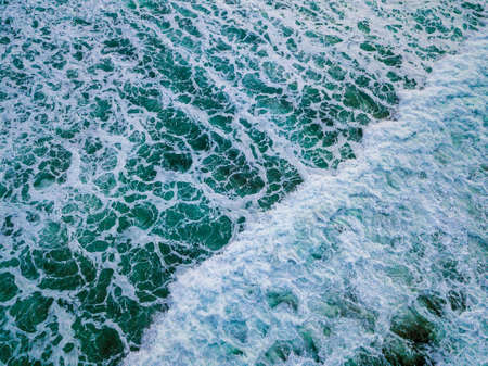 A beautiful high angle shot of a very foamy turquoise ocean water