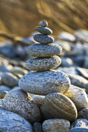 A vertical shot of stones balancing on each other with a blurred background