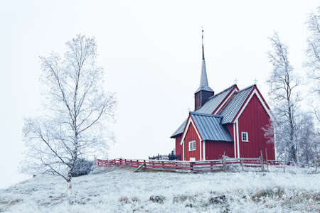 A wide shot of a red building in a snowy area surrounded by trees covered in snow under the clear sky Standard-Bild