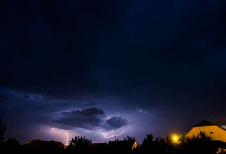 A beautiful shot of a light storm in the dark sky over a country scenery with a bright yellow lightning
