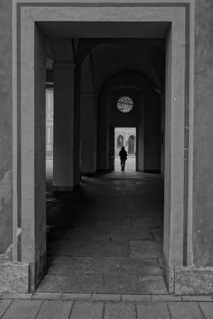 A vertical grayscale shot of a square arch and a silhouette of a person in the background - alone concept