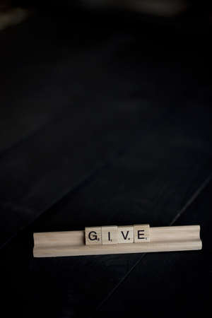 A vertical shot of wooden blocks spelling out give on a black wooden surface