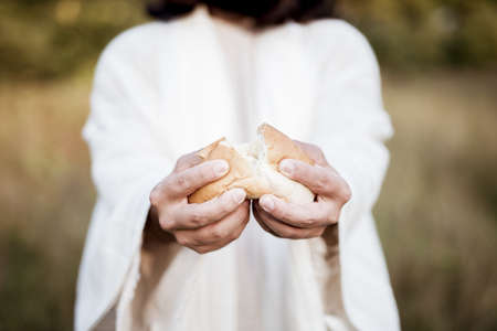 A closeup shot of Jesus Christ splitting the bread with a blurred background Stockfoto